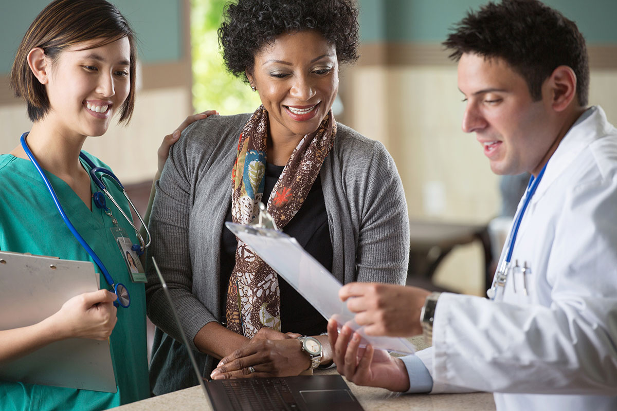 A female nurse, an African-American mother, and a male doctor reviewing a clipboard