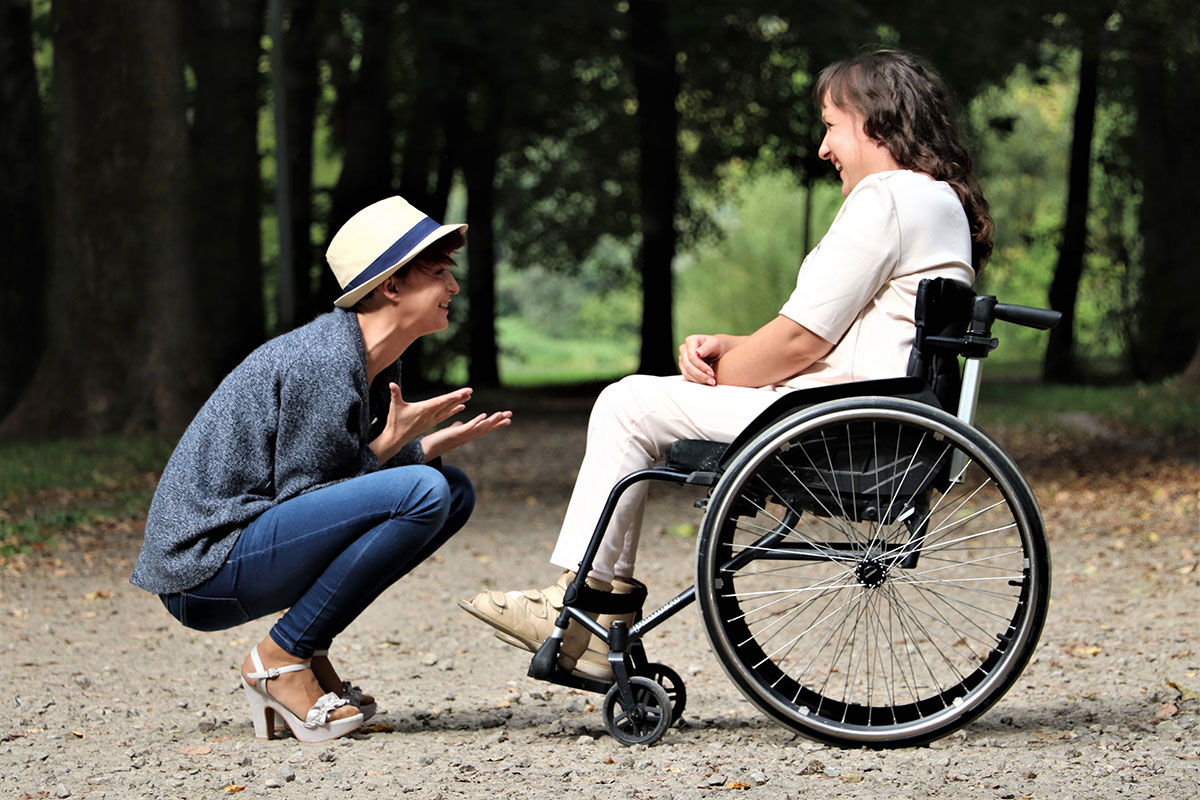 Female young adult in fedora crouching in front of female young adult in wheelchair