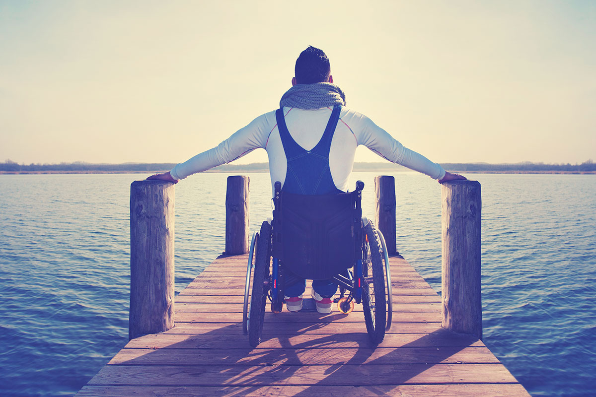 The back of a male in a wheelchair at the edge of a pier or dock