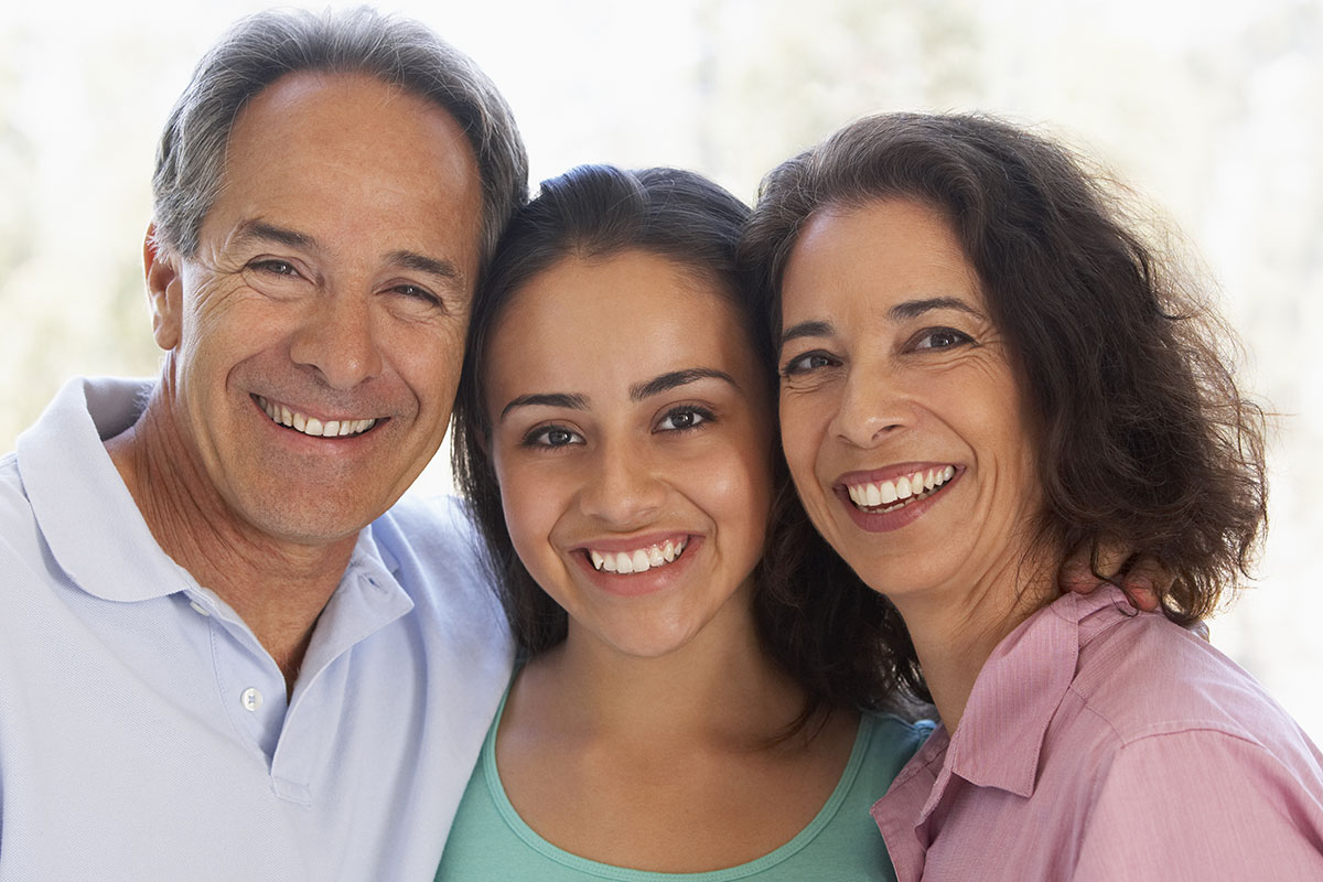 Smiling family with adult man, adult female, and young adult female in center