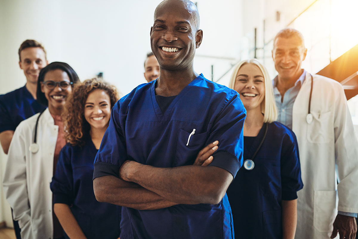 A group of smiling health care providers with a smiling African-American man in the foreground