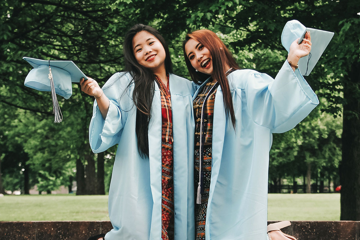 2 female Asian young adults celebrating gradiation in academic gowns