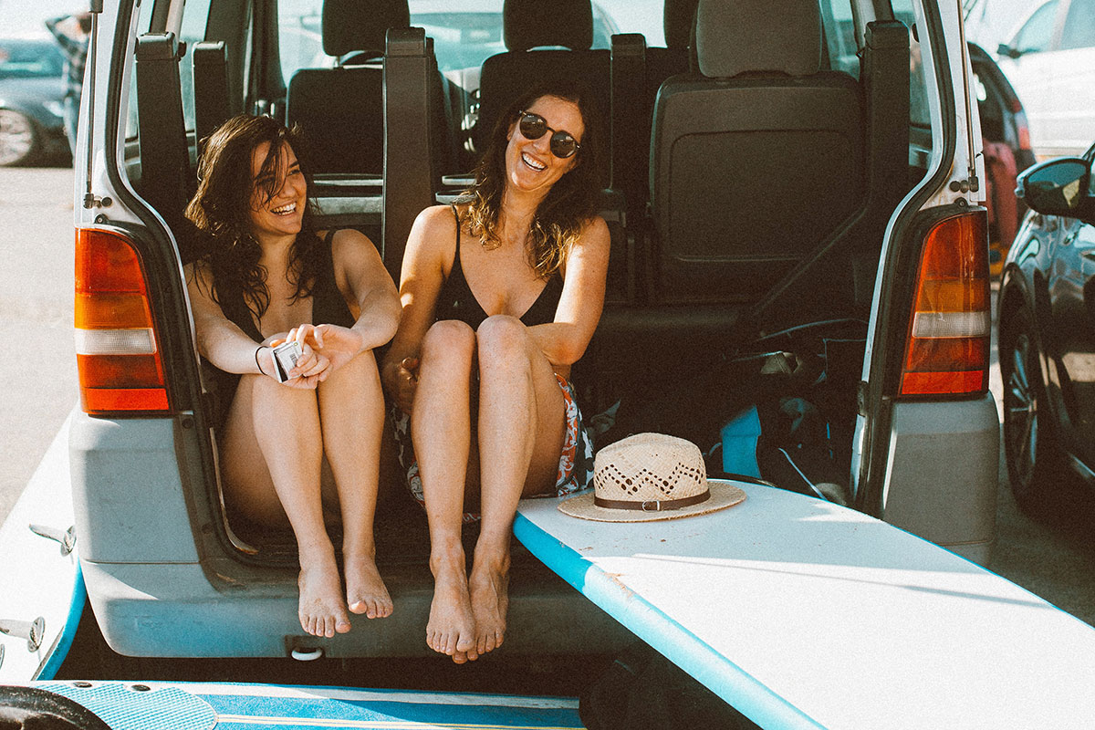 2 female white young adults sitting a car after surfing