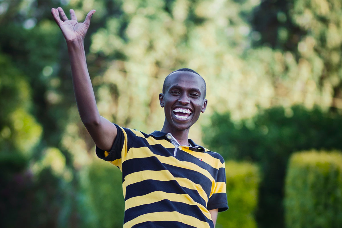 Waving and smiling African-American young adult man